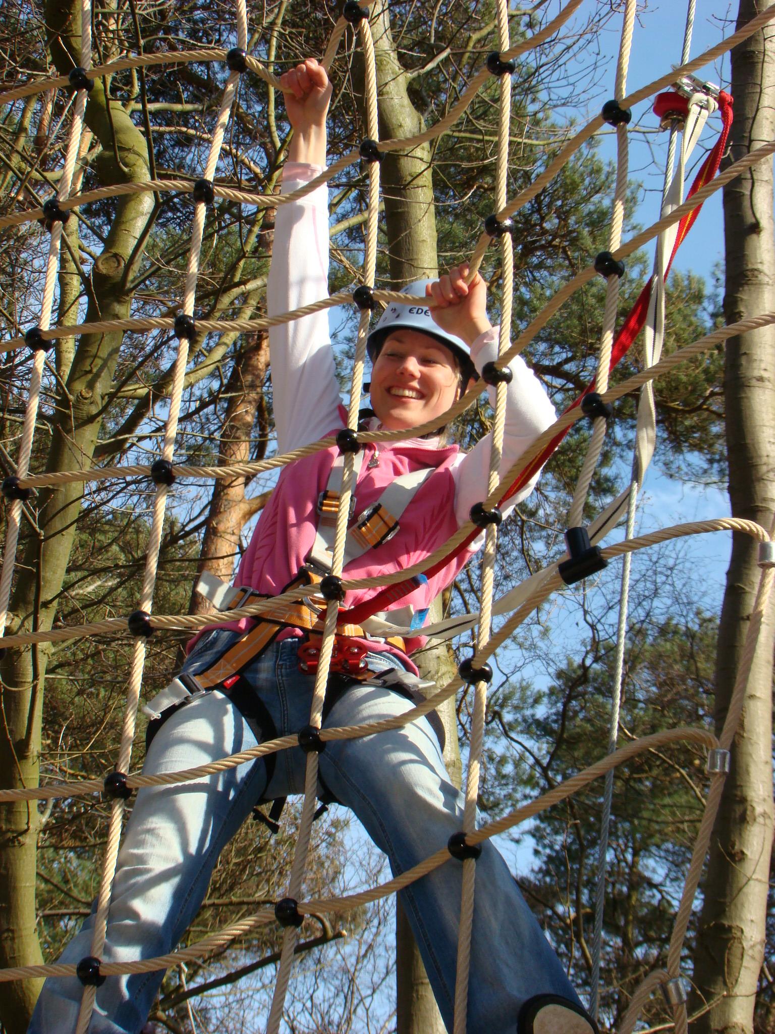 junge Frau im Kletternetz im Kletterwald BinzPora