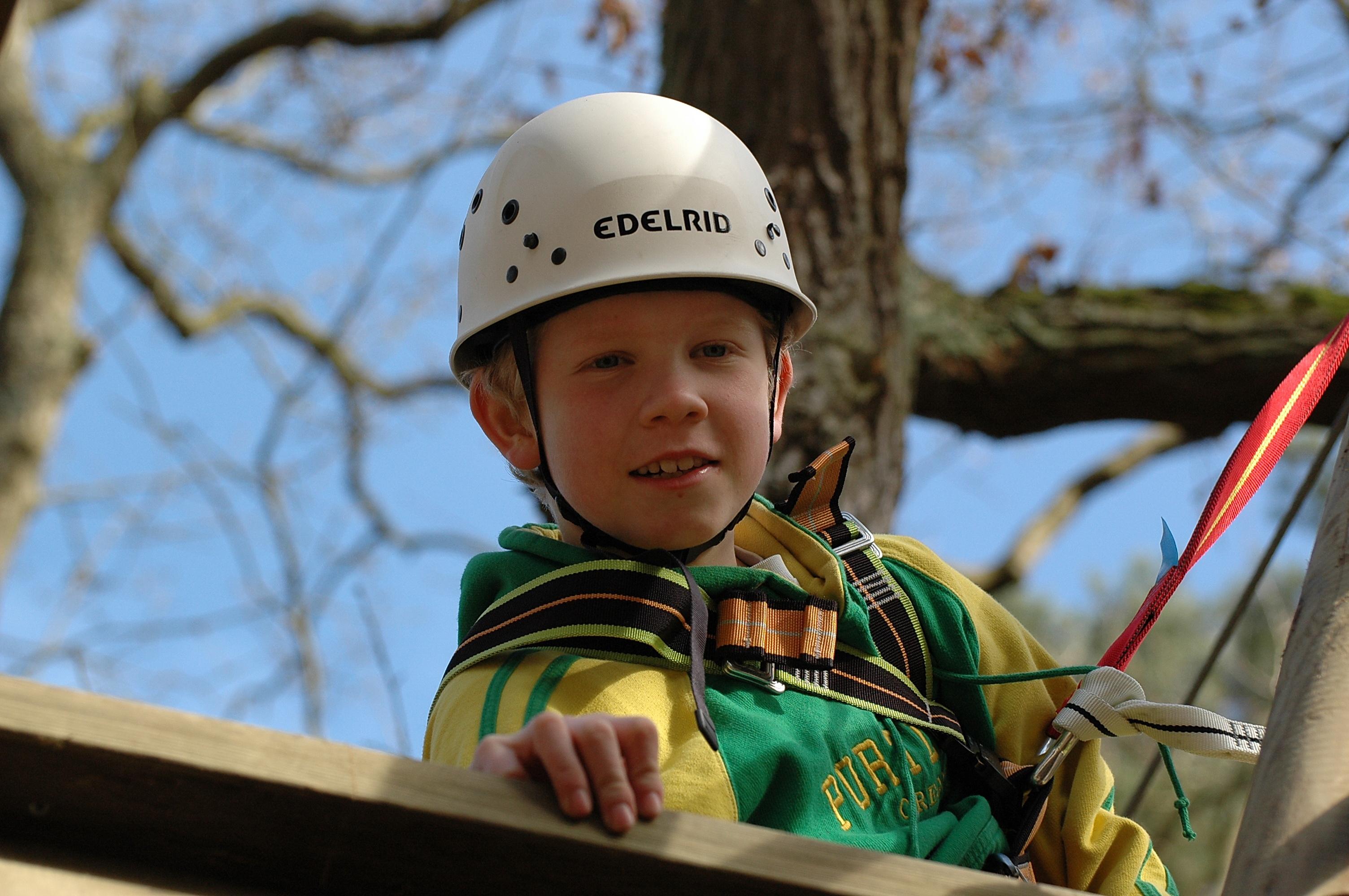 Junge mit Helm beim Klettern